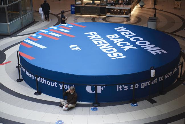 "a man sits on the floor of a mall by a large sign reading ""Welcome back friends"""
