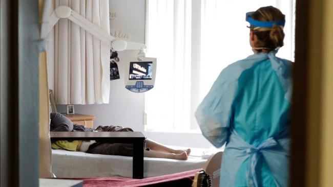 Nurse, in foreground, stands in a doorway. Someone is lying on a bed in the background.