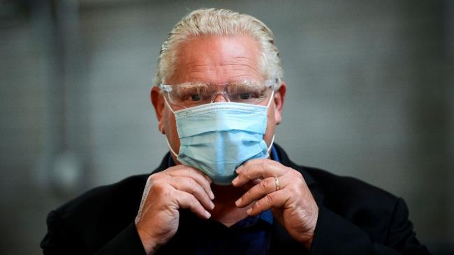 Man adjusts surgical mask on his face.