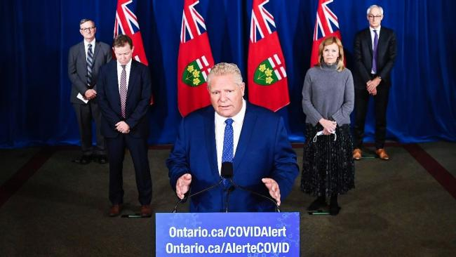 Man speaks at podium. Four people stand behind him, listening.