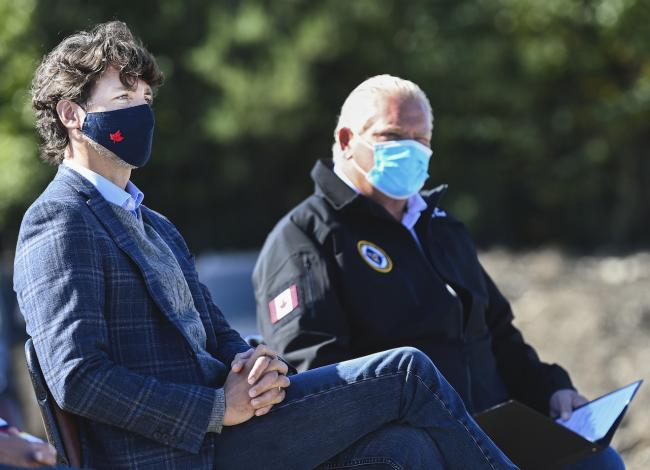 two men seating side by side wearing masks