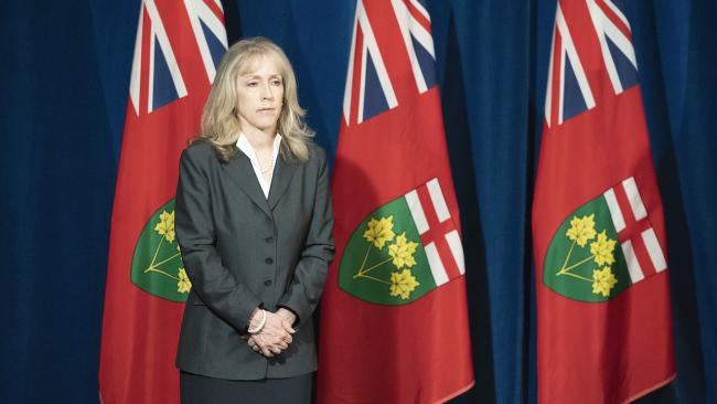 a woman in a grey suit stands in front of flags