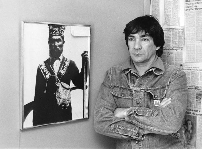 a man stands next to a portrait
