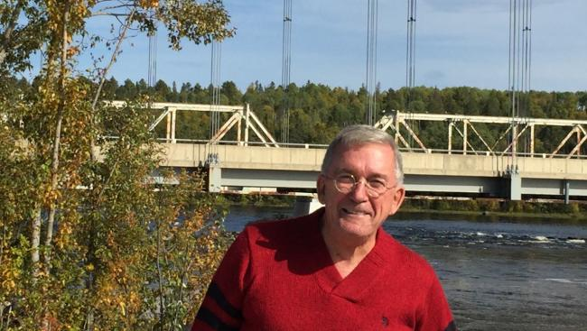 a smiling man in a red T-shirt stands in front of a bridge spanning water