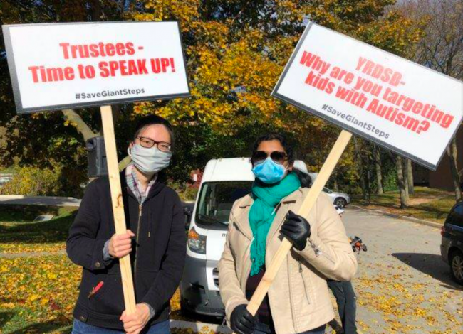 two mask-wearing protestors hold signs