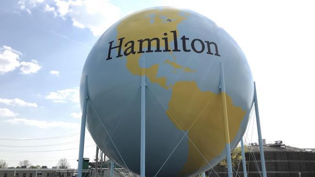 "giant blue and yellow globe reading ""Hamilton"""