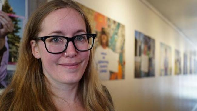 smiling woman in glasses standing in front of a row of photos