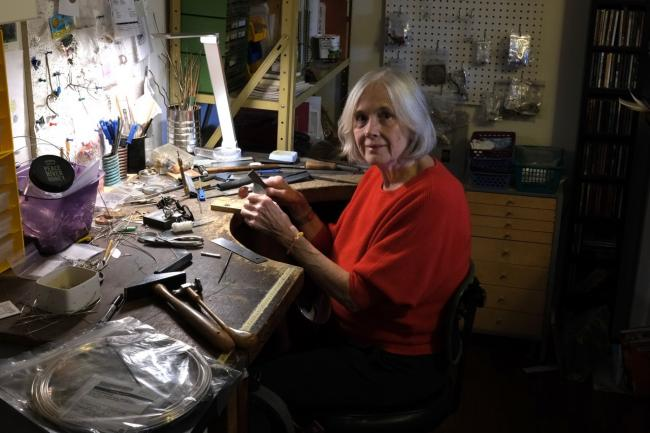 a woman sits in a jewellery workshop