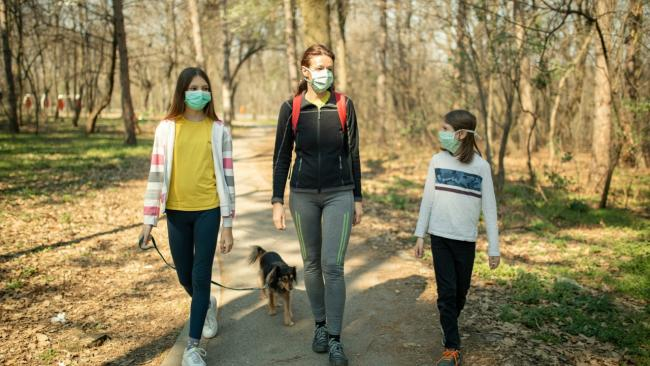 people walking in park with masks on