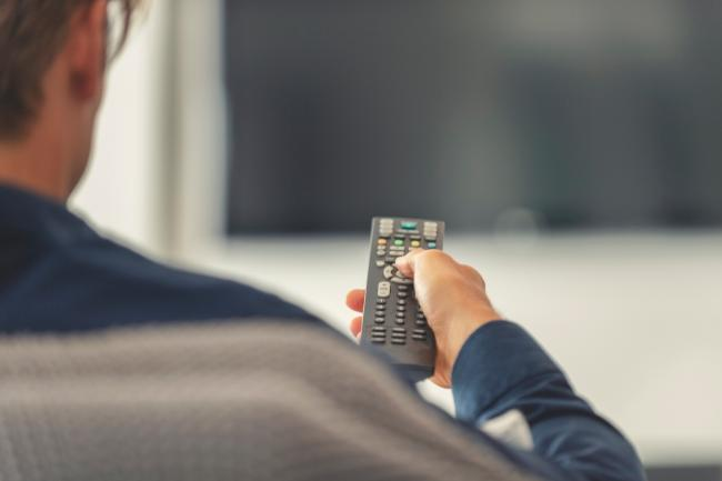 person holding a TV remote control