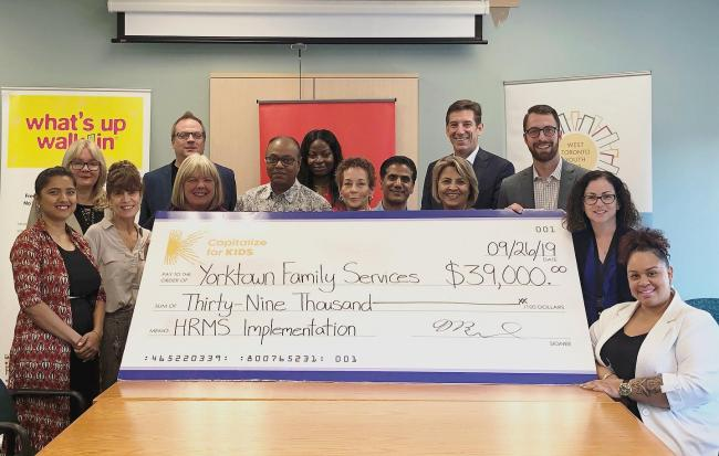 people around a table displaying a large cheque
