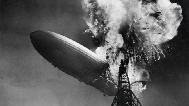 black and white photo of a blimp crashing into a tower