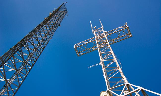 two communications towers against a blue sky