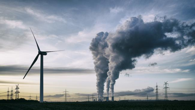 a wind turbine next to belching smoke