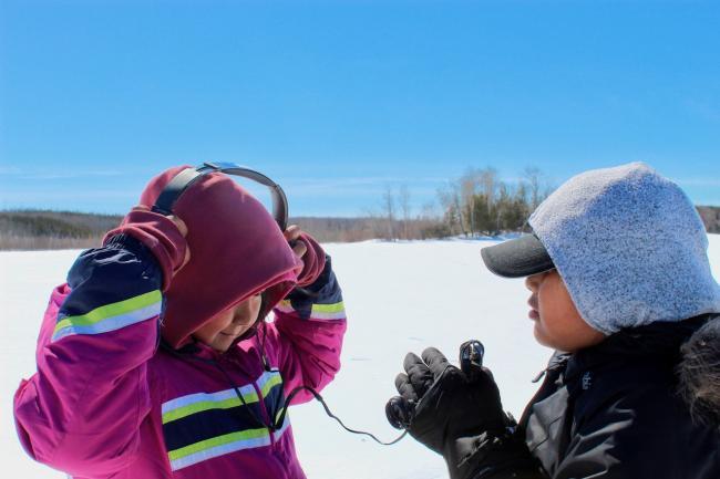 Two children use media equipment