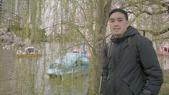 a man stands near a tree and water with paddleboats