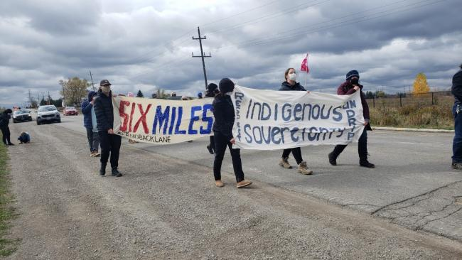 people march down a highway carrying a banner