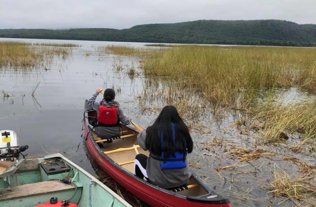 two people sit in a canoe