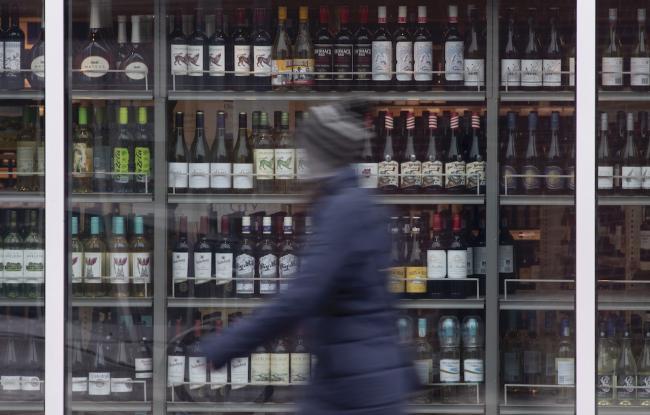 a person walks past shelves of liquor bottles