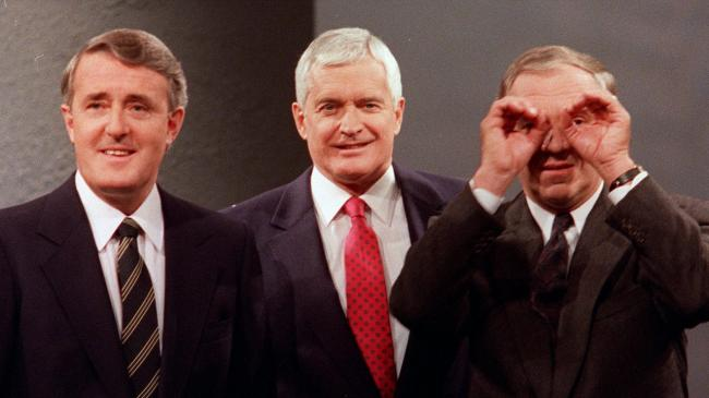 three smiling men in suits, one with hands held like binoculars to his eyes