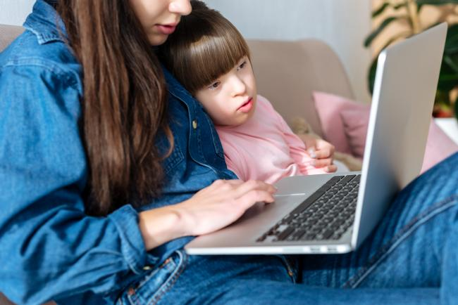 a woman and a child look at a laptop
