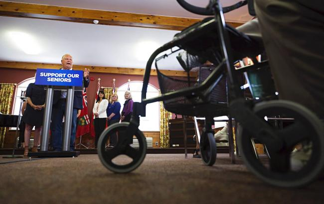 In the background, man stands behind a podium. In the foreground is a wheelchair.