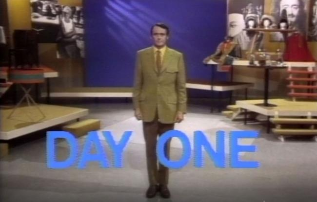 A man stands on a stage wearing a suit