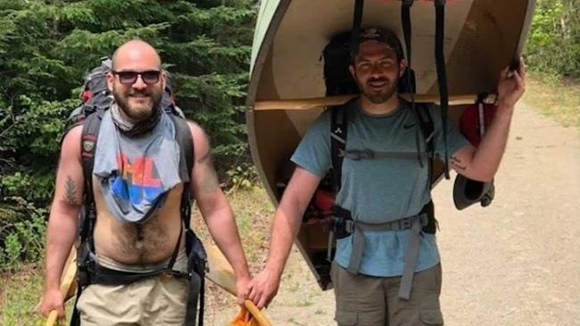 two smiling men, one holding a canoe