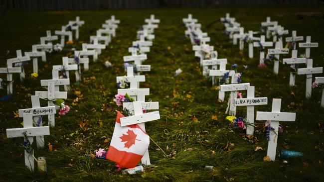 rows of white crosses with a Canadian flag in the foreground