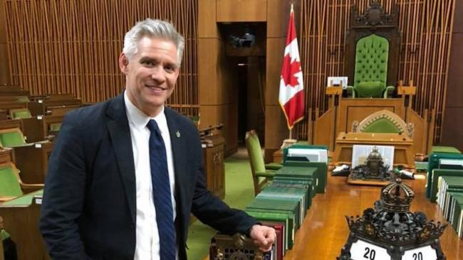 smiling man in a suit in front of a Canadian flag