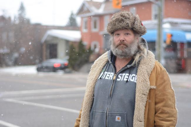 a man in a fur hat stands on a city street