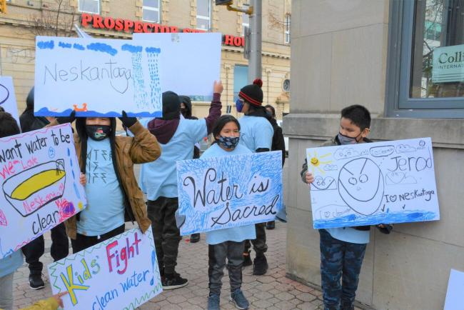 a group of young people holding signs