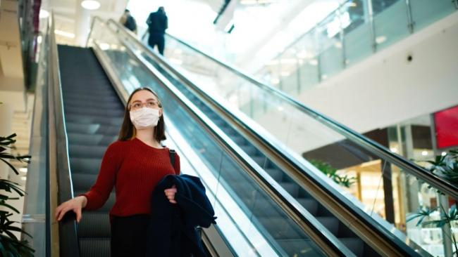 woman on escalator wearing mask