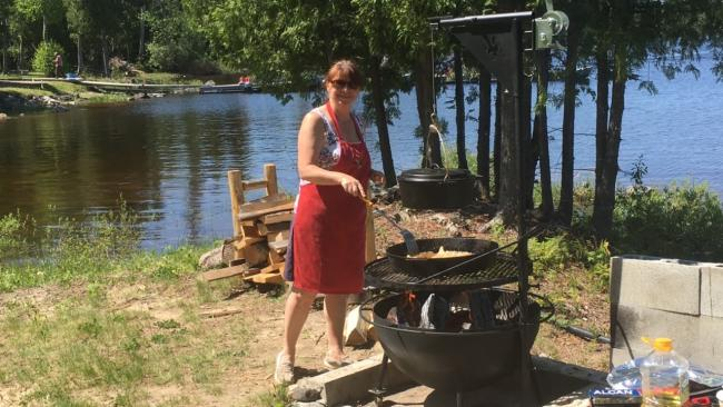 a woman in a red dress barbecues beside a lake