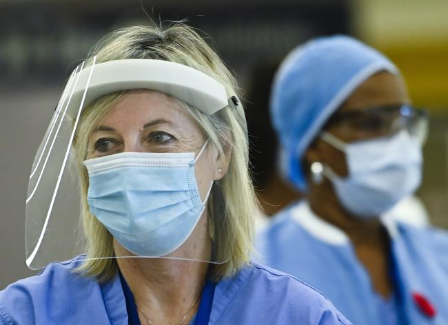 two health-care workers wearing masks and face shields