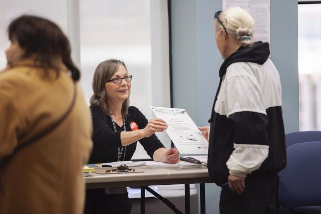 a woman hands a voter a ballot