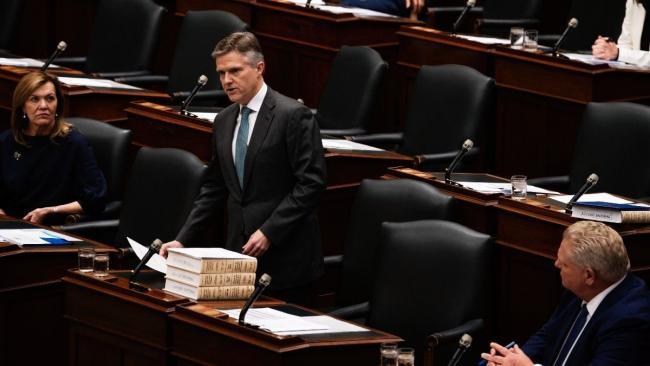 Man standing and speaking in legislature.