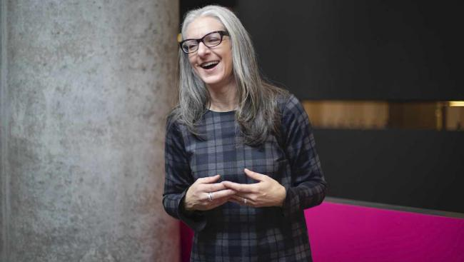 a woman with long and glasses wearing a plaid dress