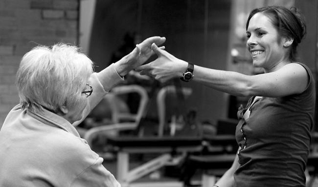 Woman helps an older woman to dance