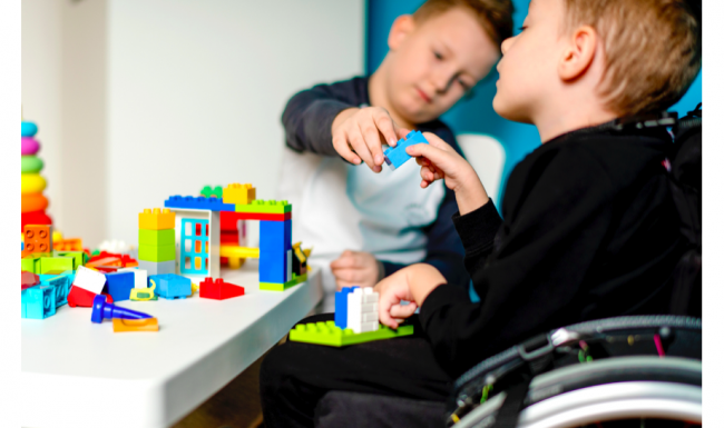 A child in a wheelchair playing with lego with another child.