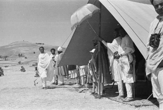 a man wearing a pith helmet stands in a tent with other men