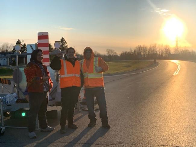Three people stand at a checkpoint at Six Nations of the Grand River