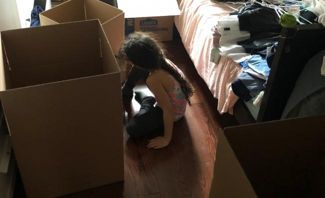 a child and moving boxes