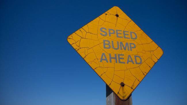 "yellow ""speed bump ahead"" sign"