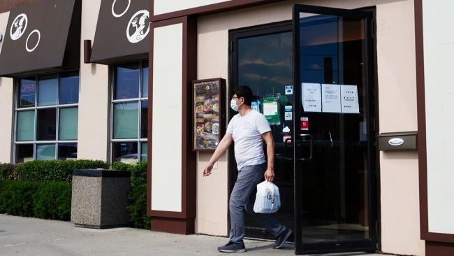 Man walks out of restaurant wearing mask and carrying plastic bag.