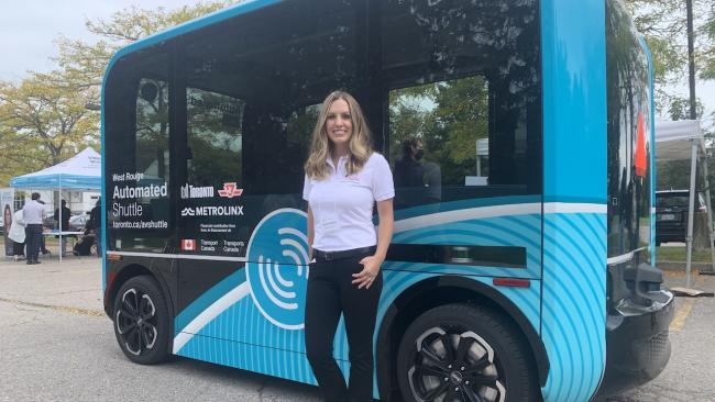 smiling, long-haired woman in front of a small blue bus
