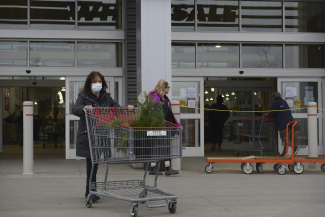 masked woman with a shopping cart outside a big-box store