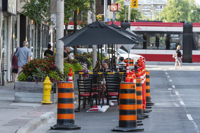 Diners eat at tables set up on the street.