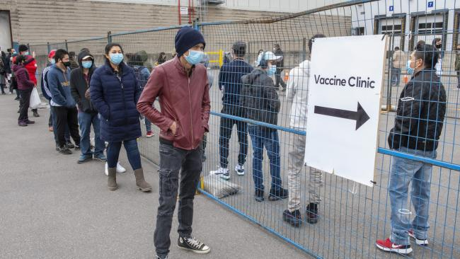 """masked people line up beside a sign reading """"vaccination clinic"""""""
