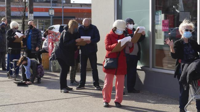 mask-wearing people in a line on a sidewalk